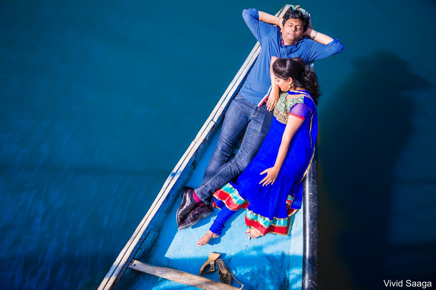 bride and groom lying in a boat during couple shoot