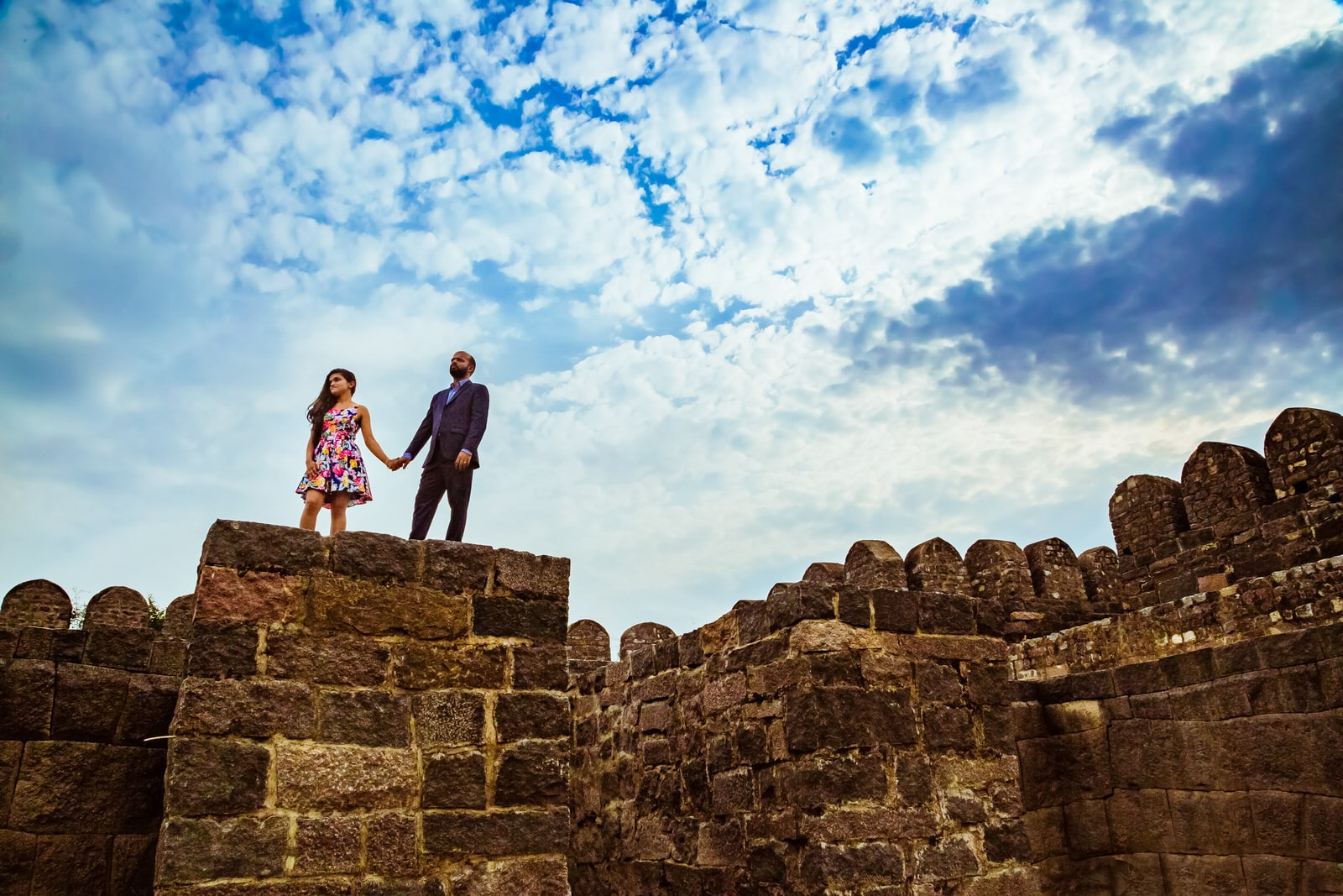 bride and groom holding hands on warangal fort wall - fashion shoot