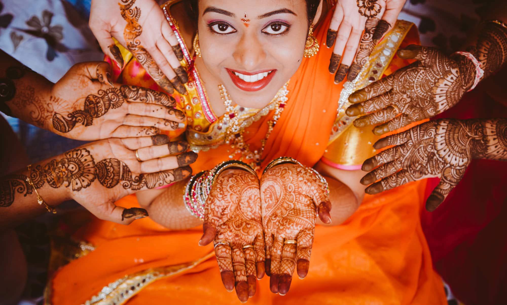 bride posing her mehndi with bride maids