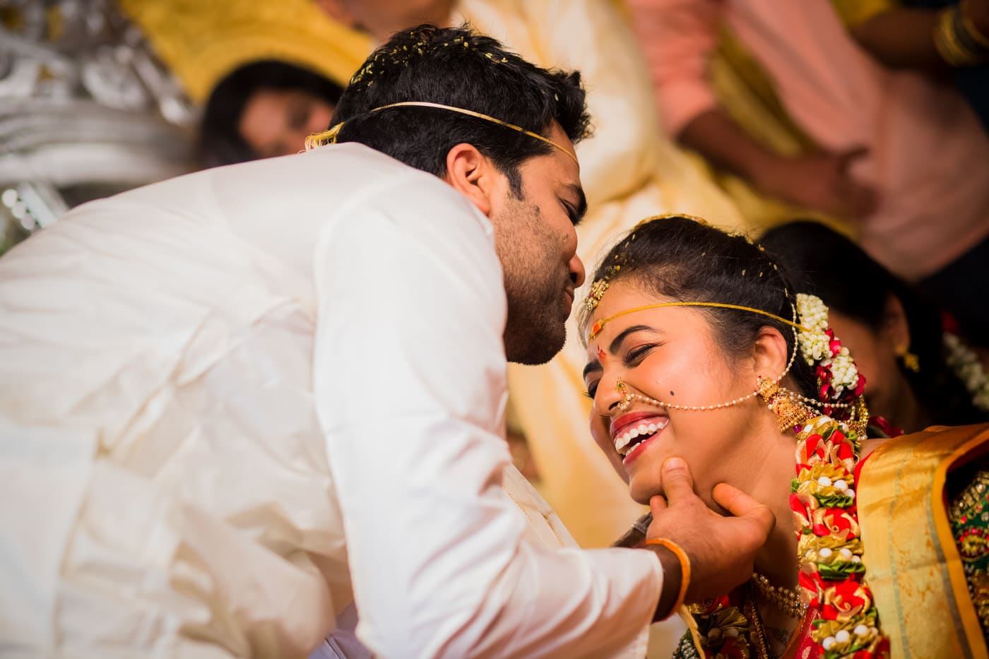 indian groom kissing his bride during wedding