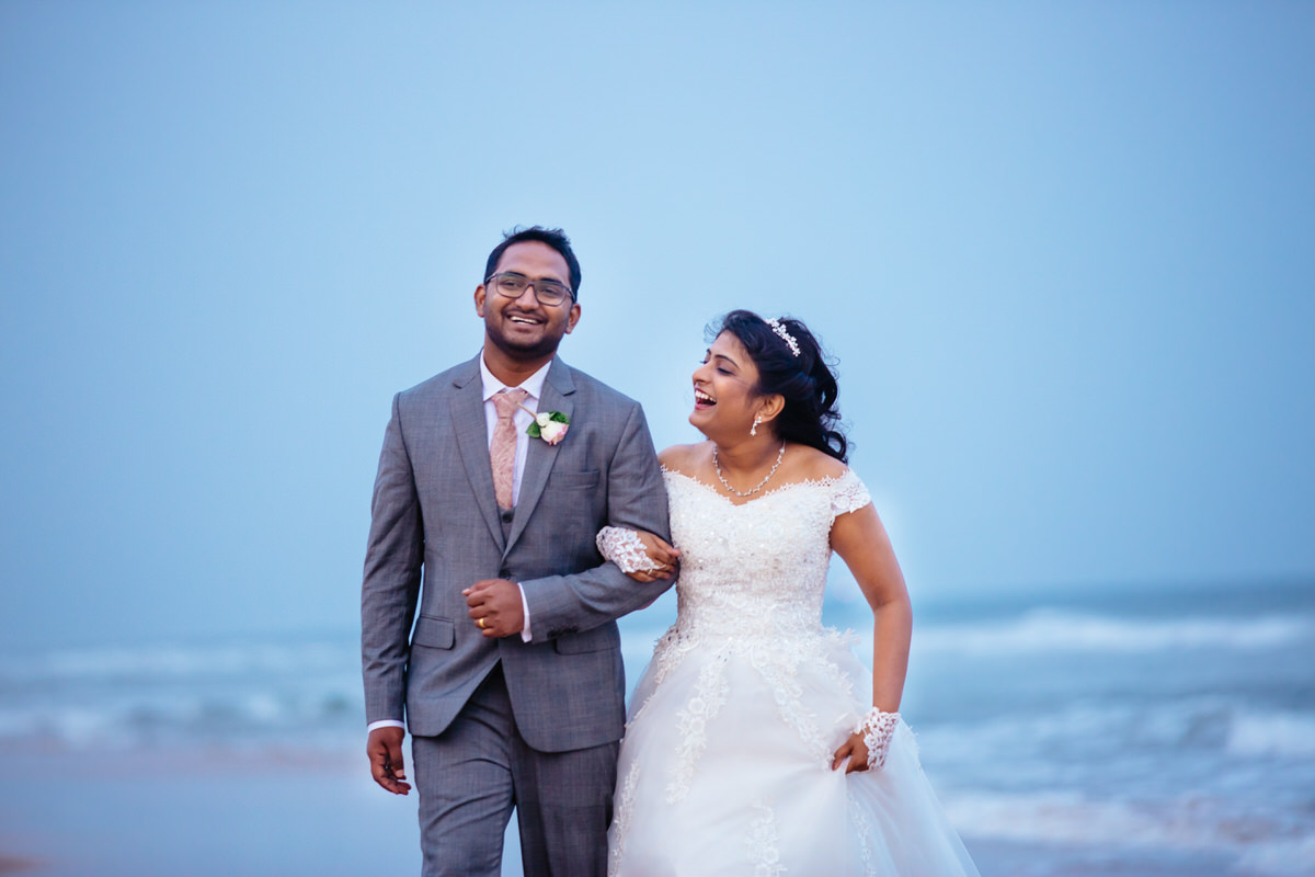 candid moment between bride and groom walking on beach